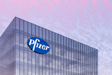 New York, The USA. February 16, 2021. Editorial Use Only, 3D CGI. Pharmaceutical Company Pfizer Signage Logo on Top of Glass Building. Workplace in High-rise Office Headquarter at Night Time.