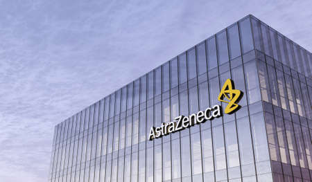Cambridge, United Kingdom. February 16, 2021. Editorial Use Only, 3D CGI. Pharmaceutical Company Astrazeneca Signage Logo on Top of Glass Building. Workplace in High-rise Office Headquarter at Night Time.
