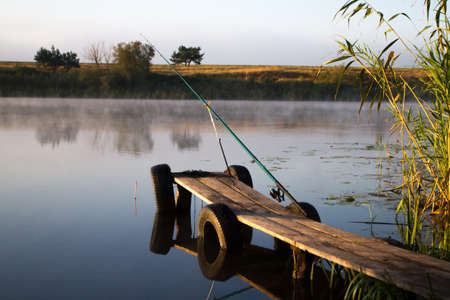 riverine: Fishing at dawn on the misty river. Water as a mirror