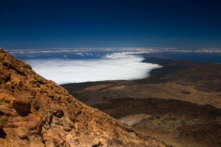 ridge of wave: From the top of the peak of Mount Teide you can see the whole island of Tenerife and the neighboring islands. The photo shows the volcano caldera, the ridge of the mountain range of the island, and at the bottom of the cloud, which go from the north. Stock Photo