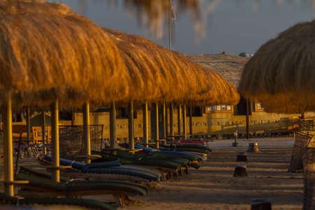 Umbrellas, beach chairs, tents on the beach in the sun when the dawn.