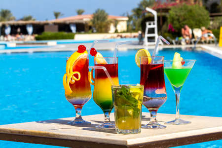 Beautiful multi-colored cocktails on swimming pool background, girls and palm trees