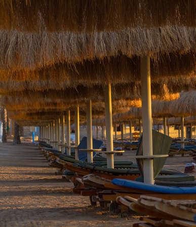 reveille: Umbrellas, beach chairs, tents on the beach in the sun when the dawn.