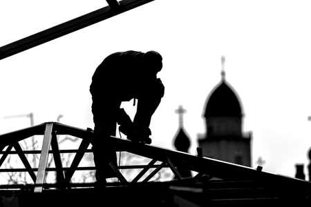 I costruttori di operai costruttori alti costruiscono un tetto all'altezza delle cupole della chiesa. Foto in bianco e nero Sagome e contorni. Un lavoratore taglia le strutture del tetto in metallo. Archivio Fotografico - 80989004