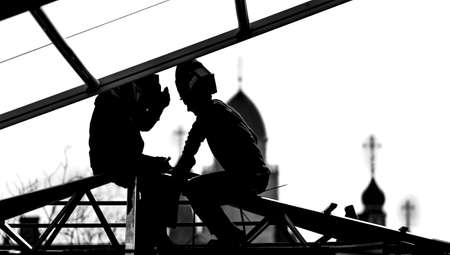Workers builders high-builders build a roof at the height of the domes of the church. Black and white photo. Silhouettes and