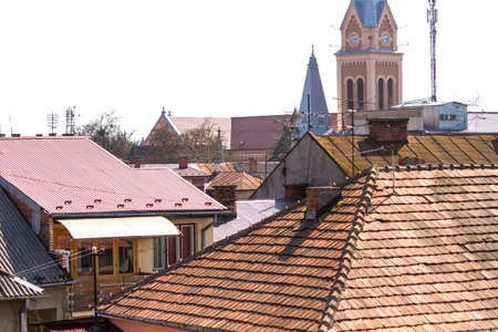 A view from above on the roofs of the old town of Mukachevo, on which sometimes there are still real chimney sweeps. Ukraine.