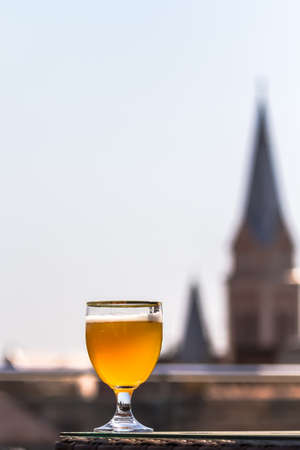 A glass of unfiltered beer looks gorgeous against the background of the old buildings of the beautiful city of Mukacheve, Ukraine Archivio Fotografico