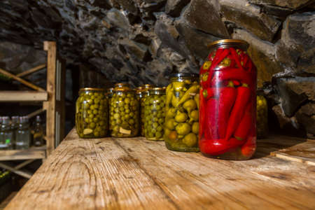 Vegetables, Preservation, pickles, marinades, in glass jars stand in a stone basement on a wooden rack.