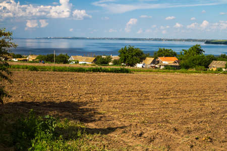 The Dnieper River, houses of Ukrainian peasants, fields, plowed fields. Ukrainian native landscapes.