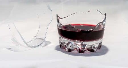 A broken whiskey glass with the remains of red wine stands on a white background. There are splinters nearby. Archivio Fotografico