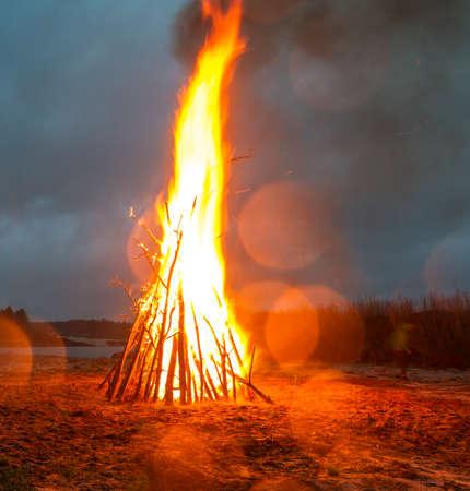 Un grande incendio brucia sulla riva di una vecchia cava piena d'acqua. Spiaggia sabbiosa, gente, acqua. Fuoco dei pionieri. Esploratori di fuoco Archivio Fotografico - 80871325