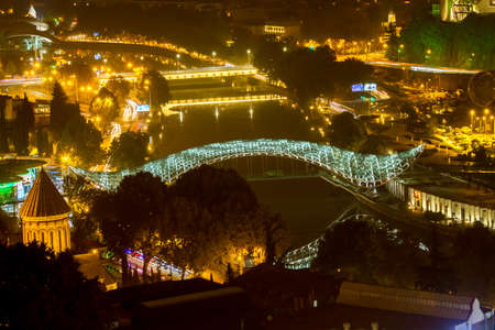 Night views of Tbilisi from the fortress. The bridge of the peace is a pedestrian bridge across the Kuru River in Tbilisi, the capital of Georgia. The bridge consists of a 156-meter steel frame, covered with glass. The whole structure is supported by 4 su