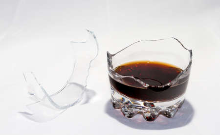 A broken whiskey glass with the remains of whiskey stands on a white background. There are splinters nearby.