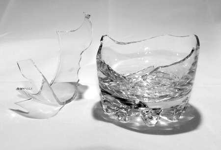 A broken whiskey glass with splinters stands on a white background.