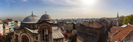 Panorama of the roofs of the old district of Istanbul with a view of the Yellow Sea and the ships standing in the roadstead. Ancient Christian church and mosques around