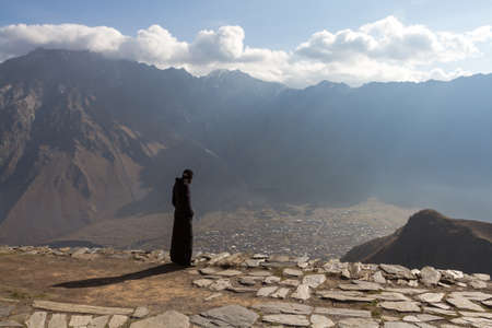 A monk from the monastery on top of a mountain looking at the valley below