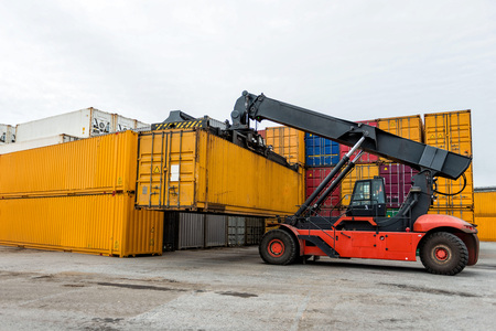 Mobile stacker handler in action at a container terminal. Stock Photo