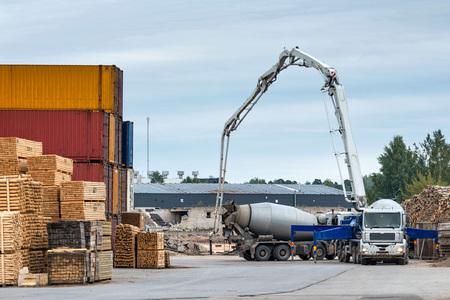materiales de construccion: Equipo de concreto trabaja fuera de la zona de almacén portuario.