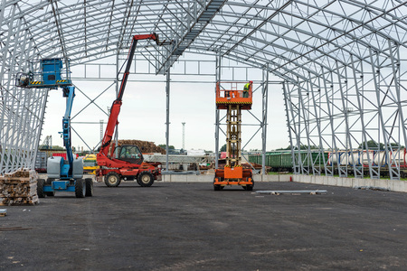 倉庫格納庫建設現場の仕事をプラットフォームを持ち上げます。 写真素材 - 75930483