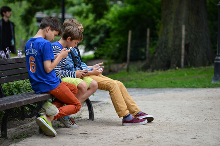 RIGA, LATVIA - JULY 27, 2016: Unknown young company sitting on a park bench and in smartphone play Pokemon Go.