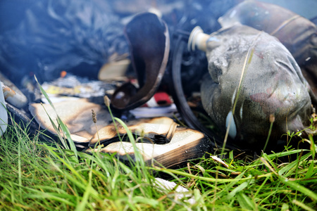 heat loss: In the grass lying fire damaged things and books.