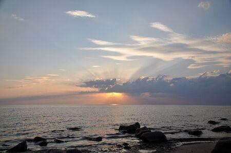 海の上雲の切れ間から太陽の光。