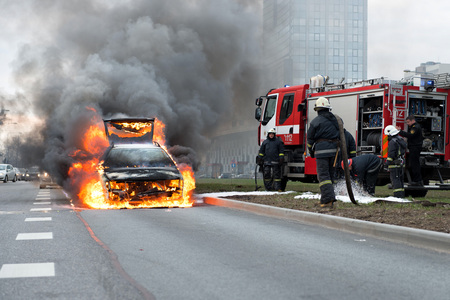 RIGA, LATVIA - APRIL 11, 2014: A few minutes in the street burnt car. Traffic is stopped. Firefighters eliminate fire.