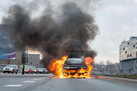 A few minutes in the street burnt car. Traffic is stopped. Firefighters eliminate fire. Reklamní fotografie