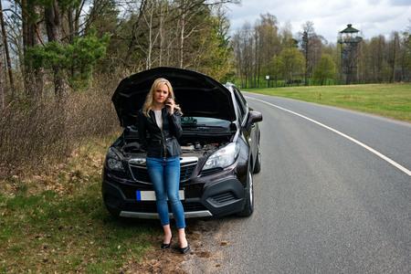 jonge aantrekkelijke wanhopige en verwarde vrouw gestrand langs de weg met kapotte auto motorstoring crash ongeval bellen op mobiele telefoon voor mechanische assistentie in verzekeringsmaatschappij concept Stockfoto