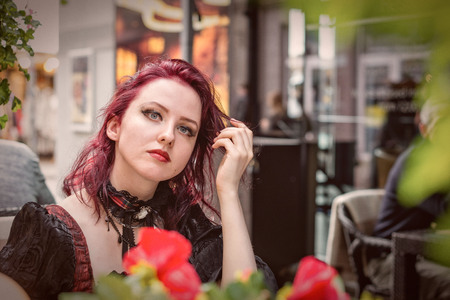 Young gorgeous redheaded woman sitting in an outdoor cafe dressed in retro fashion clothes. Stock Photo