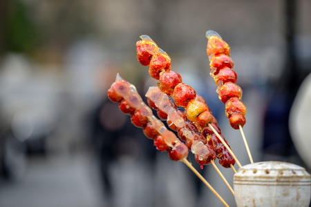 stall with caramelized fruit on stick on street Qianmen in Beijing city. Qianmen Street runs south from Tiananmen Square, just along the Beijing central axis