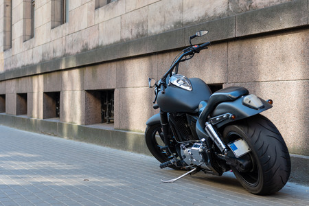 Black motorcycle with large tires on the sidewalk. Stok Fotoğraf