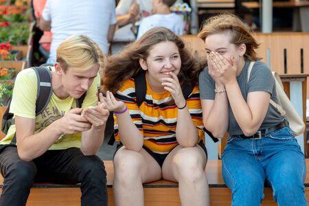 RIGA, Letonia - 26 de julio de 2018: Los adolescentes se sientan en el banco, hablan y ríen.