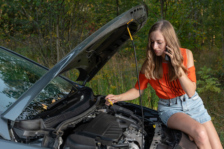 Young woman near broken car speaking by phone needs assistance - Image