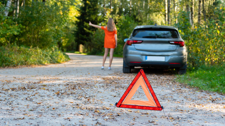 Stressful young woman driver hitchhikes and stops cars, asks for help as have problem with brocken car, uses red triangle sign to warn drivers about stop.  (selective focus) Archivio Fotografico