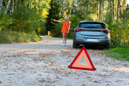 Stressful young woman driver hitchhikes and stops cars, asks for help as have problem with brocken car, uses red triangle sign to warn drivers about stop.  (selective focus) Reklamní fotografie