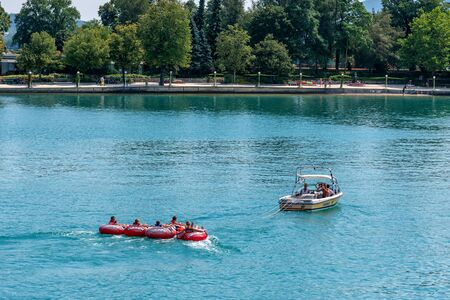 WORTHERSEE, AUSTRIA - AUGUST 08, 2018:  Happy young people, on inflatable attractions, drive behind a motorboat on the lake.
