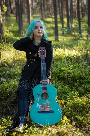 A musician with blue hair and a blue guitar resting in the park.