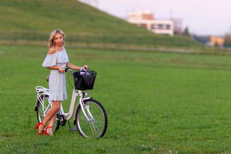 Una joven y bella mujer rubia con una bicicleta blanca en un prado verde. Foto de archivo