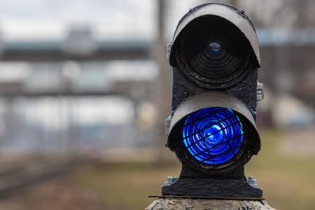 Semaphore with burning blue light. The intersection of railway tracks. - Image