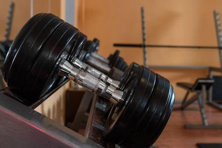 Rows of metal dumbbells on rack in the gym / sport club. Weight Training Equipment. - Image