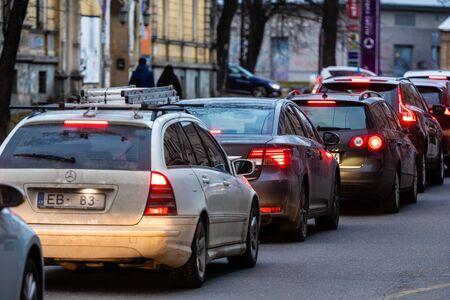 RIGA, Letonia - 27 de marzo de 2019: Atascos de tráfico en la ciudad con fila de coches en la carretera al atardecer y luces bokeh - imagen