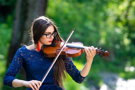 Young woman playing the violin at park. Shallow depth of field. Stok Fotoğraf