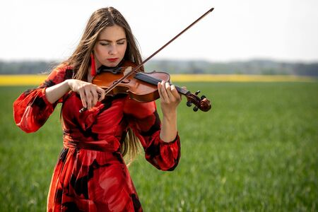 Young woman in red dress playing violin in green meadow. Banque d'images