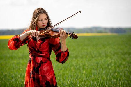 Junge Frau im roten Kleid, die Geige auf der grünen Wiese spielt.