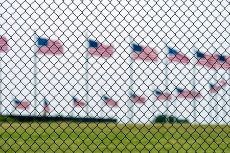 American flags at the Washington Memorial behind the wire fence. Focus on the wire fence. Archivio Fotografico