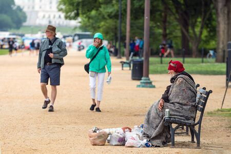 Washington DC, USA - June 9, 2019: Visitors to DC go for a stroll along the national mall. A homeless person sits on the bench at the side of the pedestrian path.
