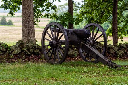A Civil War era cannon is placed behind a stone wall in Gettysburg, PA
