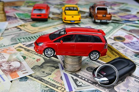 A car key and a red toy car on a tower made of coins. Background of various national currency and one symbolic gold dollar banknote.  Concept of the cost of purchasing, renting and maintaining a car - image