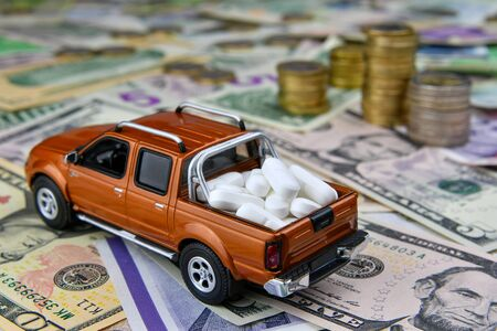 Toy pickup with tablets in a cargo box on background of different countries currency banknotes. The concept of medical availability and increasing medical expenses - image